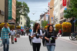 Ihmisiä kesäisellä kävelykadulla, etualalla kaksi nauravaa naista